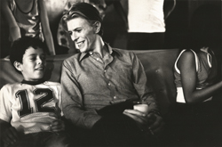 thumbnail link to original press photograph David Bowie on set 1975, on sofa next to boy, with glass of milk.